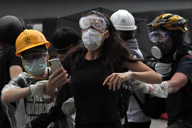In this photo taken on Wednesday, June 12, 2019, protesters flee after police fired tear gas during a massive demonstration outside the Legislative Council in Hong Kong. Young Hong Kong residents protesting a proposed extradition law that would allow suspects to be sent to China for trial are seeking to safeguard their identities from potential retaliation by authorities employing mass data collection and sophisticated facial recognition technology. (AP Photo/Kin Cheung)