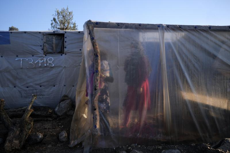 Migrants stand next to tents outside the Moria refugee camp on the northeastern Aegean island of Lesbos, Greece, on Wednesday, Jan. 22, 2020. Some businesses and public services on the eastern Aegean island are holding a 24-hour strike on Wednesday to protest the migration situation, with thousands of migrants and refugees are stranded in overcrowded camps in increasingly precarious conditions. (AP Photo/Aggelos Barai)