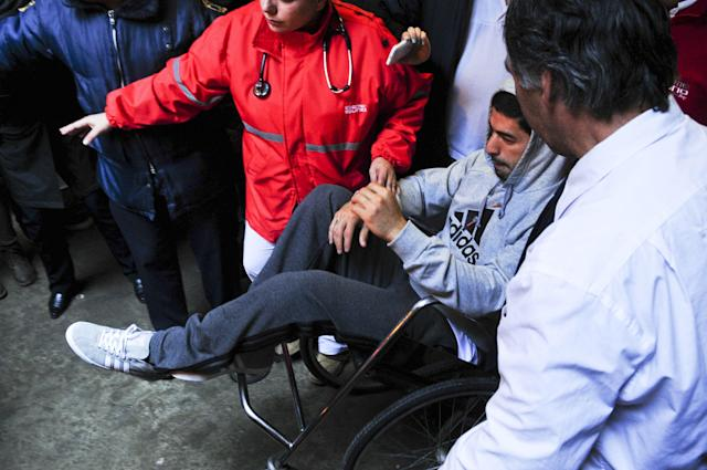 Uruguay's soccer player Luis Suarez, center, leaves a clinic in a wheelchair in Montevideo, Uruguay, Thursday, May 22, 2014. Suarez had surgery on his left knee Thursday but is expected to recover in time for the World Cup, where as one of the world's top players he is to be his team's main threat. (AP Photo/Alberto Tao) URUGUAY OUT - NO PUBLICAR EN URUGUAY