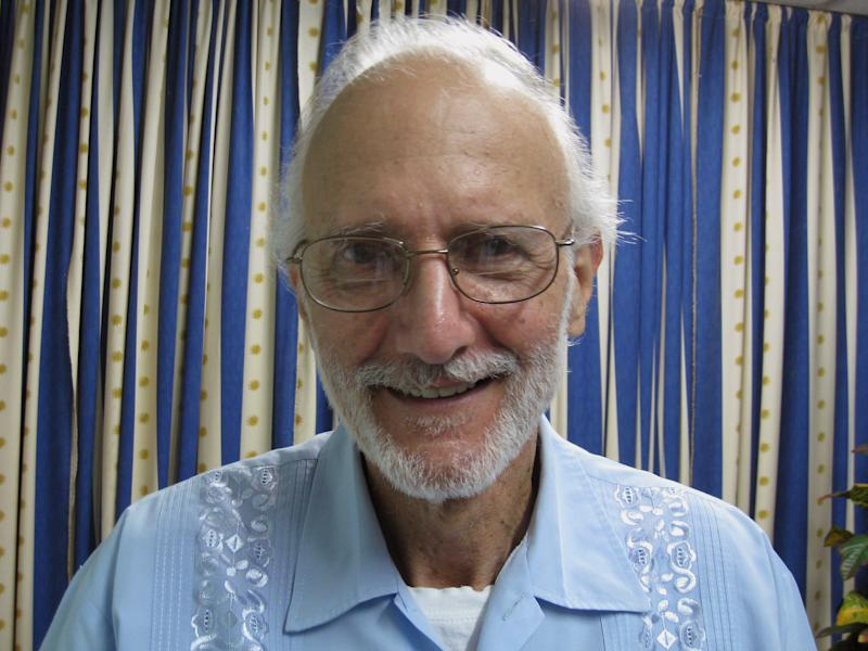 In this photo provided by James L. Berenthal, jailed American Alan Gross poses for a photo during a visit by Rabbi Elie Abadie and U.S. lawyer James L. Berenthal at Finlay military hospital in Havana, Cuba, Tuesday, Nov. 27, 2012.  Gross has settled a lawsuit against the Maryland-based company he was working for when he was arrested. The lawsuit claimed he was not properly warned about or prepared for the risks of his work. Gross and his wife filed the lawsuit against the U.S. government and Bethesda, Md.,-based Development Alternatives Inc. in November 2012. The $60 million lawsuit claimed Gross should have been provided with better information and training for his work setting up internet in Cuba.(AP Photo/James L. Berenthal)