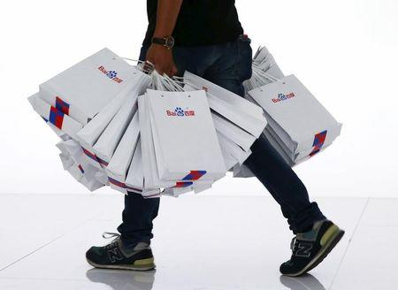 A staff carries paper bags bearing Baidu's logo at the 2015 Baidu World Conference in Beijing,