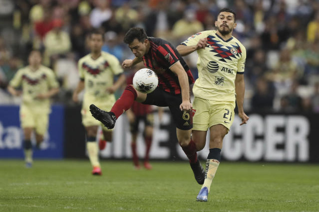 Fernando Nicolas Meza of Atlanta United, center, is challenged by Henry Martin of America during a CONCACAF Champions League soccer game at Azteca stadium in Mexico City, Wednesday, March 11, 2020. (AP Photo/Fernando Llano)