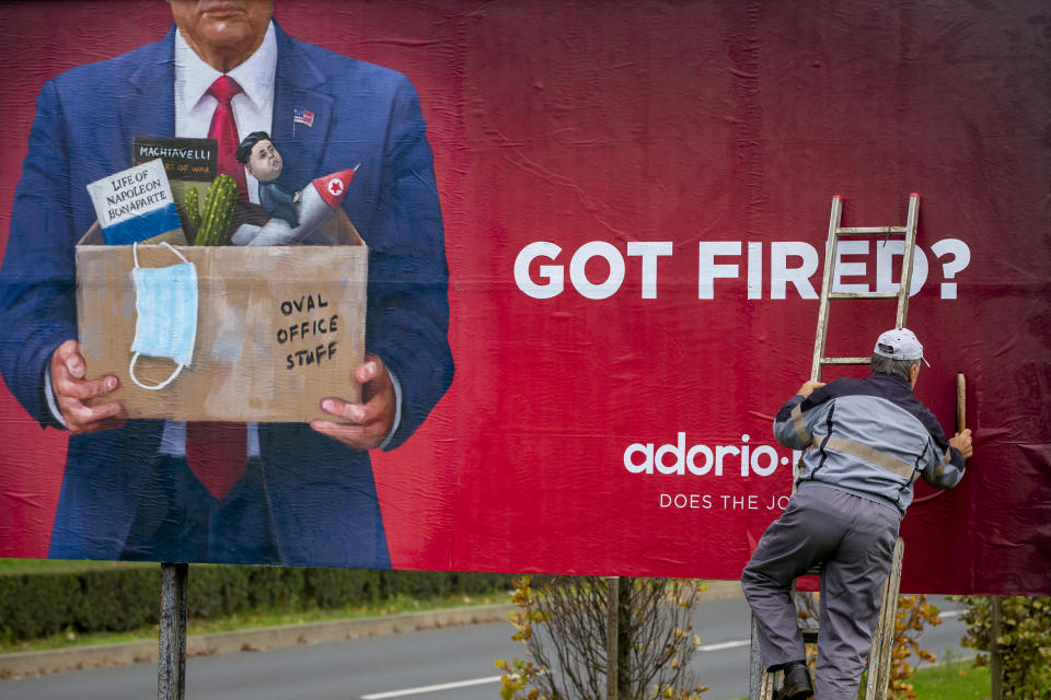 A worker puts up an advertising billboard for a recruiting company, featuring what resembles US President Donald Trump, in Zagreb, Croatia, Saturday, Nov. 7, 2020. (AP Photo/Darko Bandic)