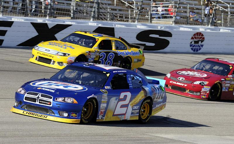 Brad Keselowski (2) comes out of Turn 4 in front of David Gilliland (38) and Travis Kvapil, right, during the NASCAR Sprint Cup Series auto race, Sunday, Nov. 4, 2012, in Fort Worth, Texas. (AP Photo/Larry Papke)