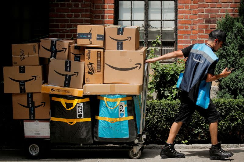 FILE PHOTO: An Amazon delivery worker pulls a delivery cart full of packages during its annual Prime Day promotion in New York