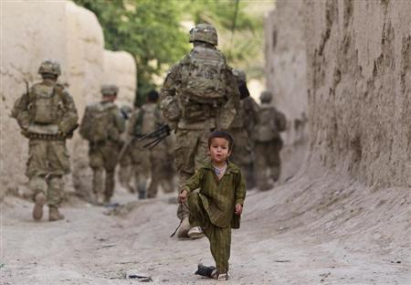 A boy plays on a street as U.S. Army soldiers of 82nd Airborne Division, patrol during a mission in Zahri district of Kandahar province