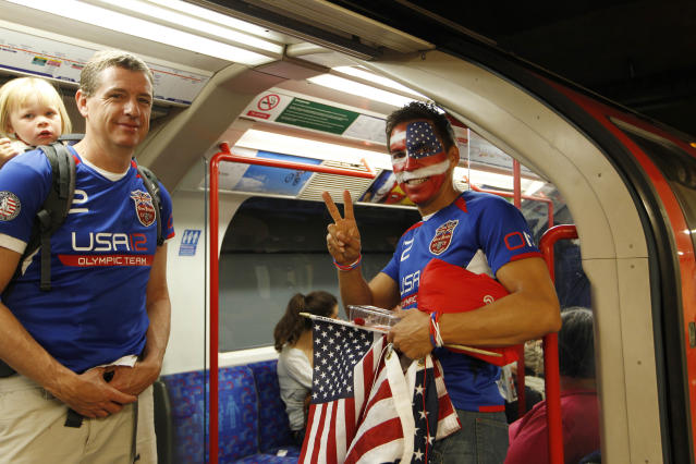 A US olympic fans one with US's flag painted on his face gestures as he travel in a Central Line underground train about to depart Mile End underground station in London, Friday, Aug. 3, 2012. Severe delays were reported Friday morning on the busy tube line serving some of the Olympics venues on the day that the athletics competition gets under way. (AP Photo/Sang Tan)