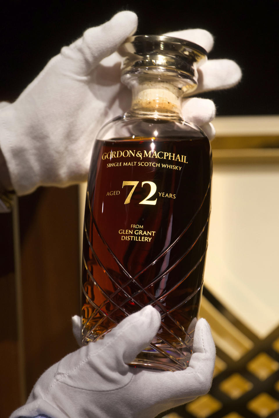 Expecting to fetch up to US$49,000 at auction, a 72-year-old bottle of Glen Grant single malt whisky from Scotland is displayed at a Bonhams auction preview in Hong Kong, Thursday, Jan. 28, 2021. Despite the economic uncertainty brought on by the pandemic, interest in the rare whisky remains high. Compared to other investment commodities, collectable whisky is doing strong in the past 10 years, with a four-fold increase in its price, Bonhams specialist Christopher Pong said. (AP Photo/Vincent Yu)