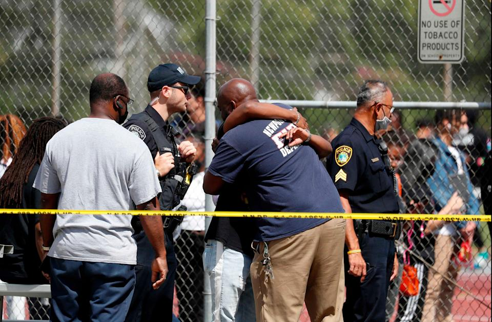 People embrace outside Heritage High School as Newport News Police are on scene responding to a shooting incident Monday, Sept. 20, 2021 in Newport News, Va.