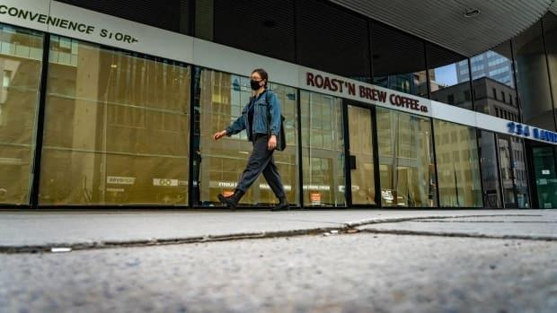 A pedestrian wearing a mask walks by a papered-up storefront on Laurier Avenue W. in downtown Ottawa. On Sunday, the city's health officials reported 91 new cases of COVID-19. (Brian Morris/CBC - image credit)