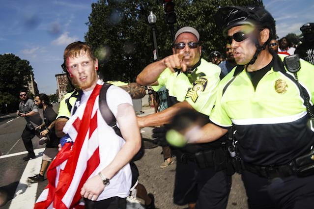 <p>A man on the left with American flag, allegedly a member of white supremacist and a participant of 'free speech rally' which held at Boston Common, is being escorted by police out of the place after the rally and being surrounded by hundreds of counter protestors heckling at him in Boston Common. (Photo: Go Nakamura via ZUMA Wire) </p>