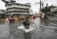 <p>A man uses sticks to move a styrofoam block he is riding along a flooded road in suburban Mandaluyong, east of Manila, Philippines, as monsoon downpours intensify while Typhoon Nepartak exits the country on Friday, July 8, 2016. (AP Photo/Aaron Favila) </p>