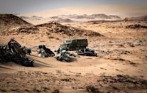 A Moroccan military truck passes vehicle wreckage in Western Sahara on November 24, after Morocco sent troops into a UN-patrolled buffer zone to reopen a road blocked by a group of separatists