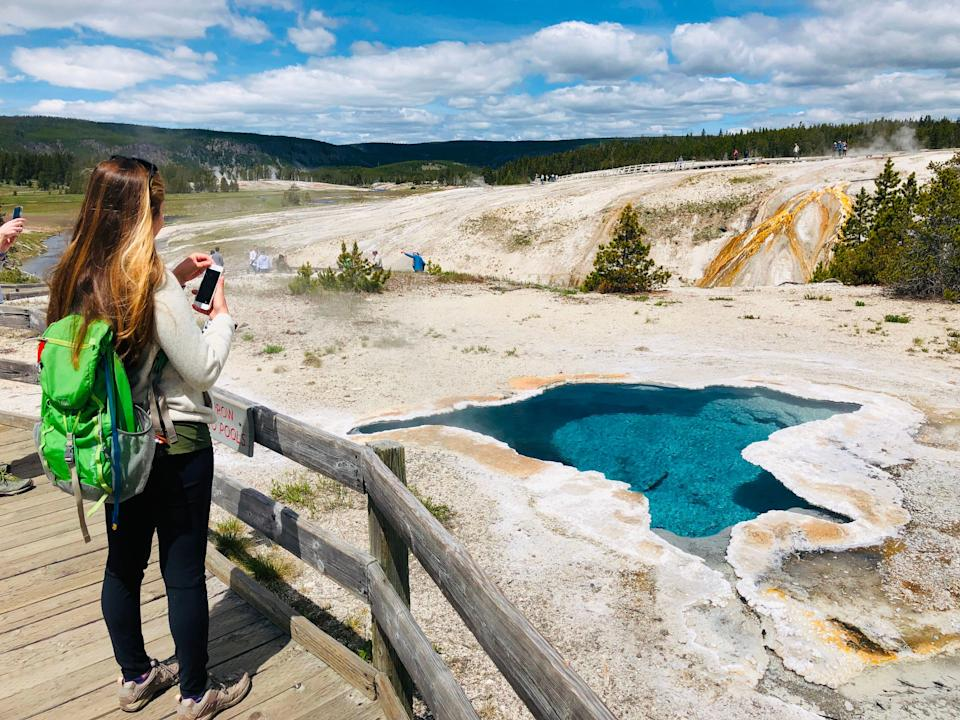 A woman takes photos of Blue Star spring near Old Faithful Upper Geyser Basin in Yellowstone National Park. (Photo: DANIEL SLIM via Getty Images)