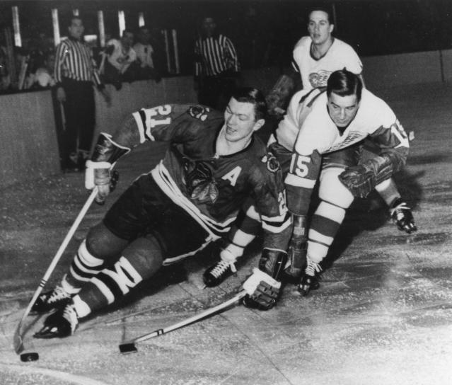 FILE - In this Feb. 24, 1965, file photo, Chicago Blackhawks' Stan Mikita, left, pulls away from Detroit Red Wings' Ted Lindsay during an NHL hockey game in Chicago. A posthumous study of Mikita's brain shows the hockey Hall of Famer suffered from chronic traumatic encephalopathy at the time of his death a year ago. Dr. Ann McKee, the director of the BU CTE Center, announced the findings during the Concussion Legacy Foundation's Chicago Honors Dinner on Friday, Sept. 13, 2019, at the request of Mikita's family. (AP Photo/File)