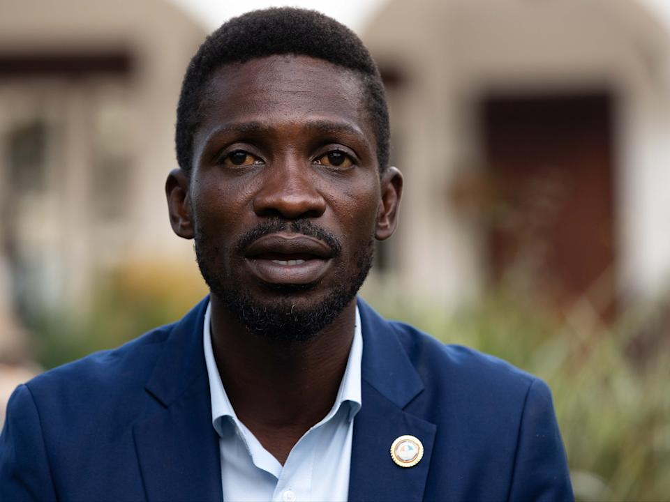 <p>Wine speaks to reporters as security forces surround his home on 15 January (the day after the election) in Kampala, Uganda</p> (Getty)