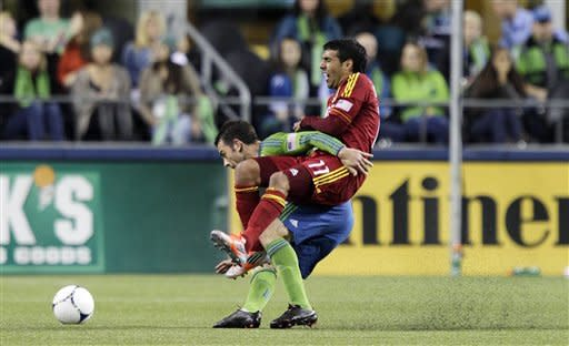Real Salt Lake's Javier Morales (11) tangles with Seattle Sounders' Zach Scott during the first half of an MLS soccer match, Wednesday, Oct. 17, 2012, in Seattle. Scott received a red card on the play and was ejected from the match. (AP Photo/Ted S. Warren)