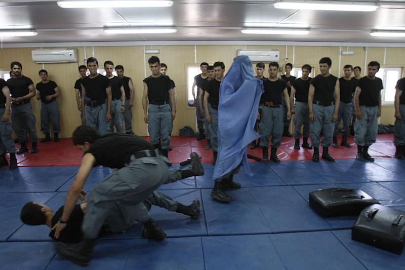 Newly graduated Afghan national police officers demonstrate their skills during a graduation ceremony at a National Police training center in Jalalabad, east of Kabul, Afghanistan, Thursday, June 14, 2012. Over 190 National police officers graduated after receiving 4 months of training in Jalalabad. (AP Photo/Rahmat Gul)