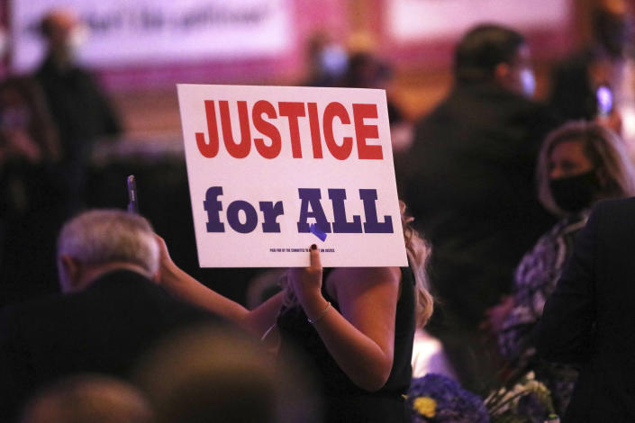 "A member of the audience holds a ""Justice for All"" sign during West Virginia Gov. Jim Justice's election night watch party at The Greenbrier Resort, Tuesday, Nov. 3, 2020, in White Sulphur Springs, W.Va. (AP Photo/Chris Jackson)"