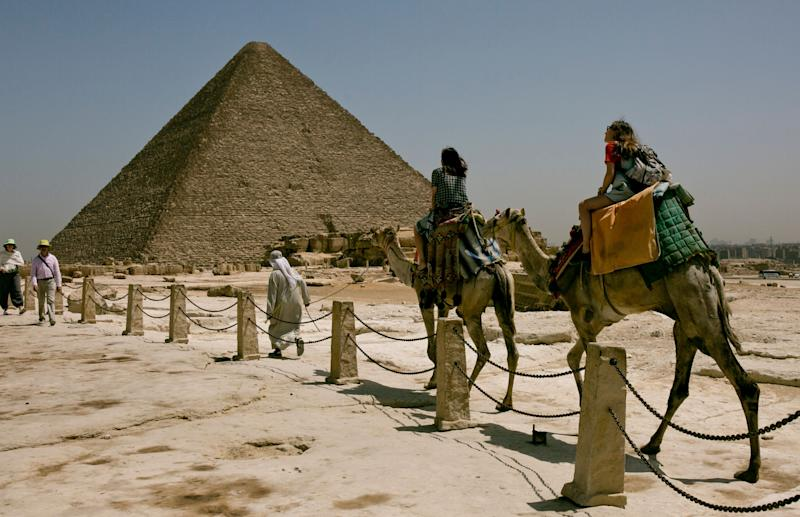 Tourists ride camels during a visit to the Giza Pyramids, near Cairo, Egypt, Tuesday, May 21, 2019, two days after a tour bus struck an improvised explosive device near the site, wounding more than a dozen foreign tourists. (AP Photo/Maya Alleruzzo)