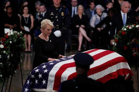 Cindy McCain, wife of late U.S. Senator John McCain, leans over his casket as his body lies in state inside the U.S. Capitol Rotunda in Washington, U.S., August 31, 2018. REUTERS/Eric Thayer
