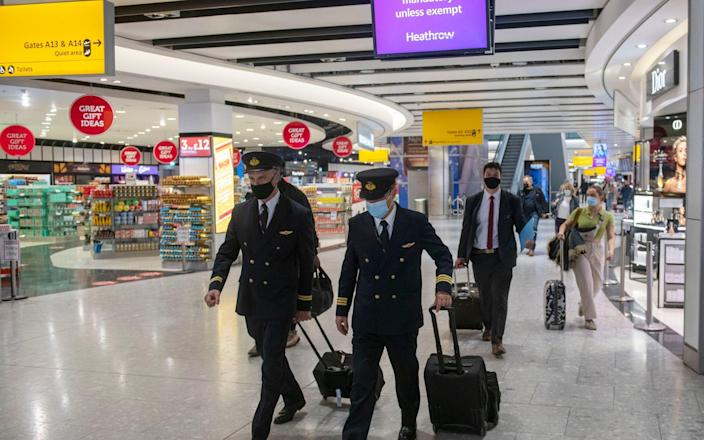 Aircrew in masks in the departure lounge make their way to the aircraft - Geoff Pugh for The Telegraph