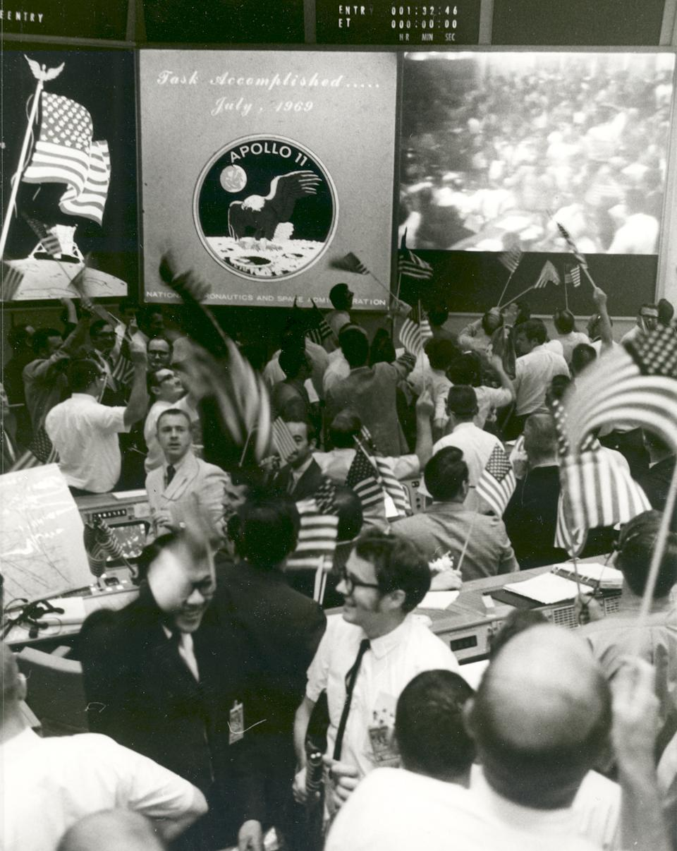 Overall view of the Mission Operations Control Room in the Mission Control Center, Building 30, Manned Spacecraft Center, showing the flight controllers celebrating the successful conclusion of the Apollo 11 lunar landing mission on July 24, 1969.  (Photo: NASA)