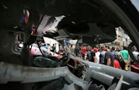 The bomb blast in Baghdad set nearby shops on fire and left debris including the charred, twisted remains of a vehicle in the street