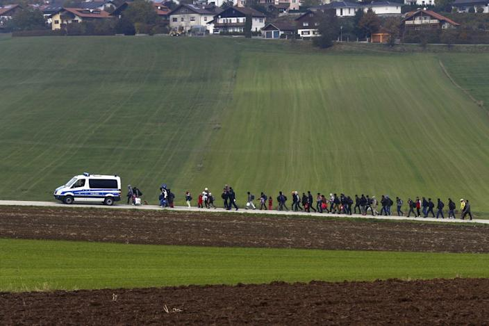 <p>Immigrants are escorted by German police to a registration center after crossing the Austrian-German border in Wegscheid, Germany, Oct. 20, 2015.<i> (Michael Dalder/Reuters)</i></p>