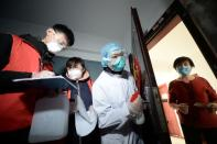 Community workers and medical staff visit a woman at her home as they conduct door-to-door search to inspect residents in Tianjin