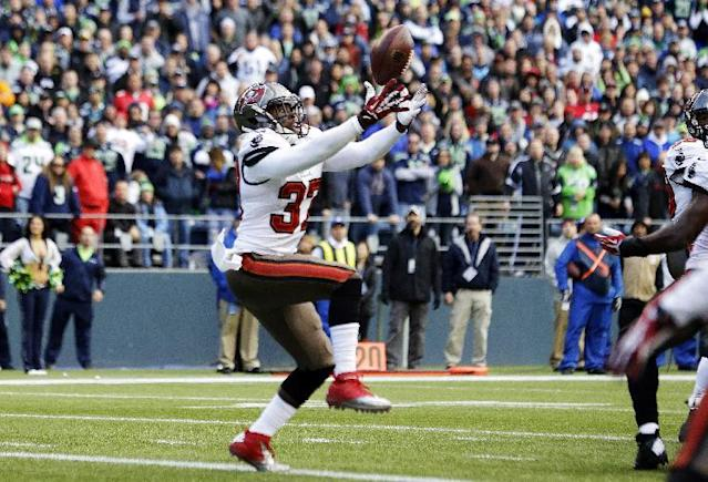 Tampa Bay Buccaneers defensive back Keith Tandy intercepts a pass from Seattle Seahawks quarterback Russell Wilson in the second half of an NFL football game Sunday, Nov. 3, 2013, in Seattle. (AP Photo/Elaine Thompson)