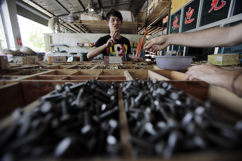 In this May 26, 2012 photo, Yang Shihan, 20-year-old grandson of the business's owner of the Yang family's car parts and hardware store attends a customer in Houqiao, near the Myanmar border, Yunnan Province, China. Many still expect that the lifting of U.S. and European Union economic sanctions against Myanmar will boost trade from China's industrial regions through Ruili and other border areas in Yunnan, a mostly mountainous province that has close ties with all its Southeast Asian neighbors. (AP Photo/Eugene Hoshiko)