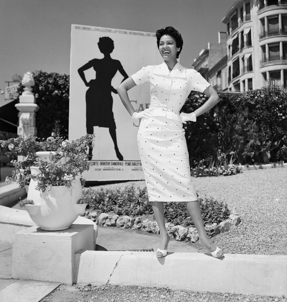 """Dandridge poses in front of a poster for her movie """"Carmen Jones"""" in 1955 at the Cannes Film Festival in France."""