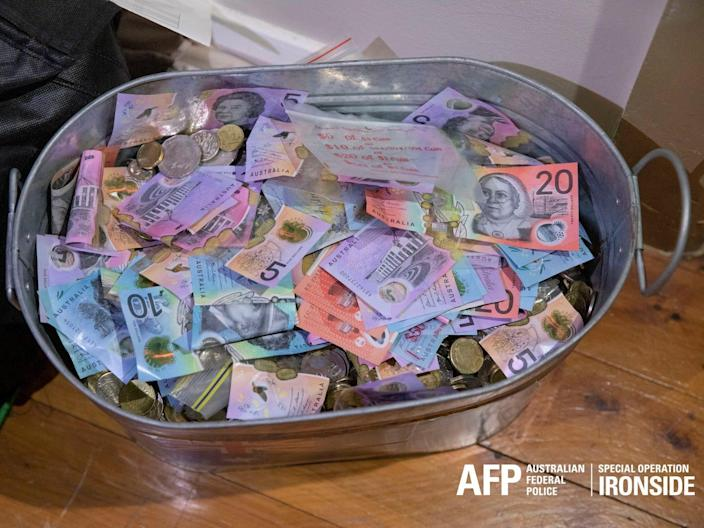 A top-down view over a metal bucket filled with cash, in an Australian police handout photo.