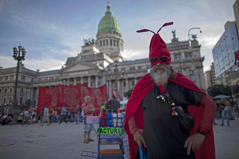 A retiree dressed as an ant protests the comprehensive judicial reform proposed by President Cristina Fernandez outside Congress in Buenos Aires, Argentina, Wednesday, April 24, 2013. Lawmakers began debating major changes to the country's justice system Wednesday. Lawmakers began debating major changes to the country's justice system Wednesday. Some of the changes would end indefinite injunctions against government actions, expand and popularly elect most of the magistrate's council and require executive, legislative and judicial authorities to publish their tax declarations online. (AP Photo/Natacha Pisarenko)