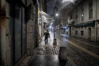 A man walks in the street at the start of the new curfew to counter the COVID-19 in the center of Lyon, central France, Saturday, Jan. 16, 2021. All of France will be under a stricter curfew starting Saturday at 6 p.m. for at least 15 days to fight the spread of the coronavirus. (AP Photo/Laurent Cipriani)