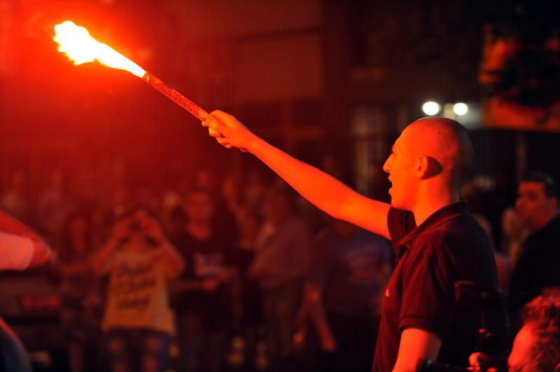 An extreme far-right Golden Dawn party's supporter holds a flare during the elections results in the northern Greek port city of Thessaloniki, Sunday, May 6, 2012. Golden Dawn, which has vowed to kick out immigrants and mine Greece's borders with Turkey, was predicted to win between 6.5-7.5 percent, well above the 3 percent needed to enter parliament. (AP Photo/Nikolas Giakoumidis)