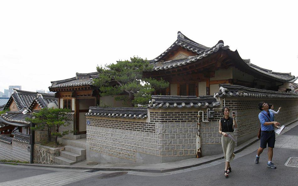 People take pictures at Bukchon Hanok Village, a traditional village in Seoul