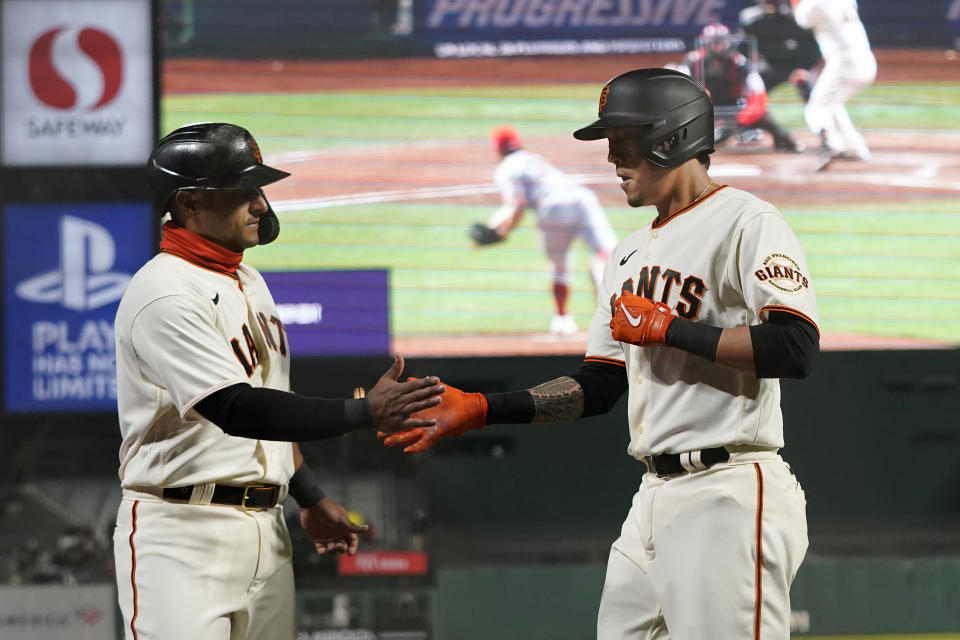 San Francisco Giants' Wilmer Flores, right, is congratulated by Donovan Solano after hitting a sacrifice fly that scored Solano during the seventh inning of the team's baseball game against the Cincinnati Reds in San Francisco, Tuesday, April 13, 2021. (AP Photo/Jeff Chiu)