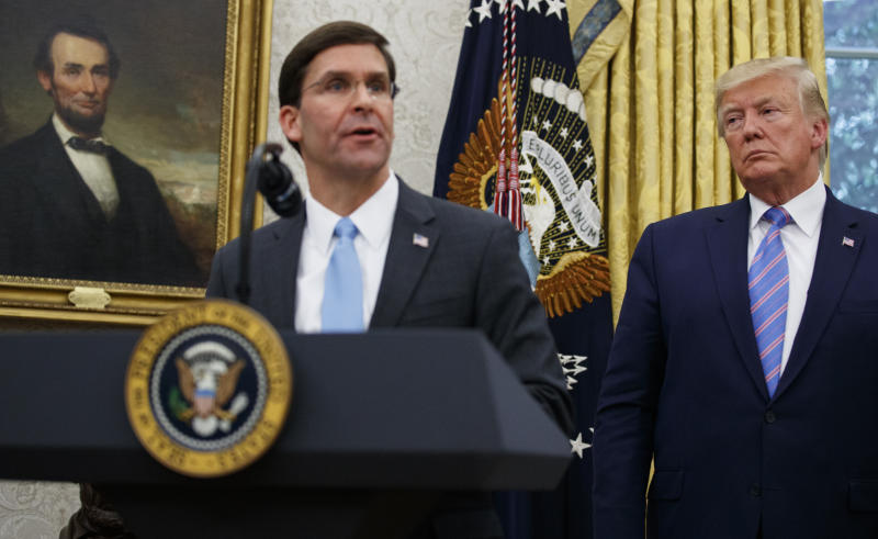 President Donald Trump looks to Secretary of Defense Mark Esper during a ceremony in the Oval Office at the White House in Washington, Tuesday, July 23, 2019. (AP Photo/Carolyn Kaster)