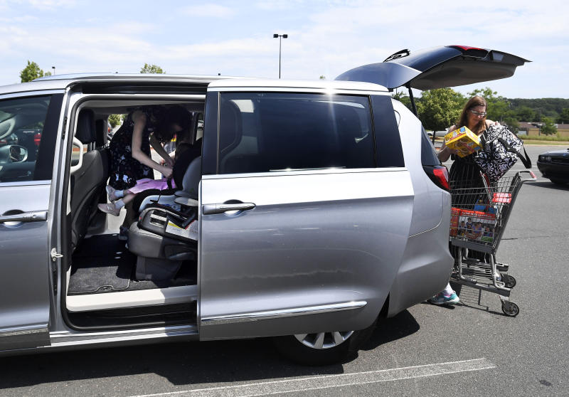 In this Tuesday, July 16, 2019, Melanie Matcheson loads groceries into her Chrysler Pacifica as her daughter Georgianna buckles little sister Caroline into her car seat at a shopping area in Southington, Conn. Melanie bought an eight-passenger silver Pacifica in mid-June for about $31,000, getting an $8,000 discount. (AP Photo/Jessica Hill)