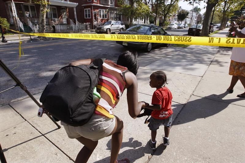 "Neighbors duck under police tape near 1415 Kaighn Ave.,  in Camden, N.J., Wednesday, Aug. 22, 2012.  Police say a New Jersey mother apparently decapitated her 2-year-old boy and put his head in the freezer of their home before she fatally stabbed herself. Chevonne Thomas, 33, called 911 just after midnight to say something had happened to her child and it ""sounded like she had done it,"" said Jason Laughlin, a spokesman for the county prosecutor's office. Officers found Zahree Thomas' body on the first floor of the Camden home and the boy's head in the freezer. The mother stabbed herself in the neck with a kitchen knife and died, Laughlin said. (Photo/Mel Evans)"