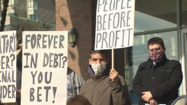 People gather outside a business in New Westminster B.C. on Saturday Mar. 13, 2021 to protest rules around short-term, high interest loans in Canada. (Maggie MacPherson/CBC News - image credit)