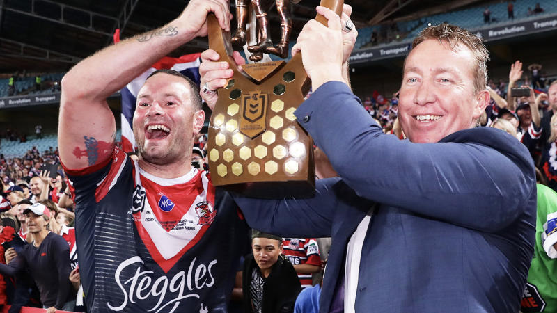 Roosters coach Trent Robinson (pictured right) lifting the NRL trophy.