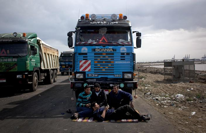 FILE - In this Friday, Feb. 22, 2013 file photo, Egyptian truck drivers sit by their vehicles as protesters blocked the road leading to the east port preventing loaded trucks from leaving the port, during day six of a general strike, in Port Said, Egypt. For nearly two weeks, protesters and strikers have shut down much of Egypt's Mediterranean city of Port Said, filling the streets with one angry rally after another. Opponents of Egypt's Islamist president are looking to Port Said as a model for stepping up their campaign against him with a possible wave of civil disobedience in other parts of the country. (AP Photo/Nasser Nasser, File)