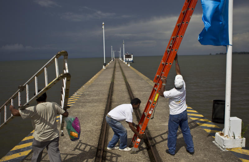 In this June 7, 2013 photo, workers position a ladder to hang a banner on a wharf surrounded by Lake Nicaragua, in Granada, Nicaragua. A multi-billion dollar Chinese plan to plow a massive rival to the Panama Canal across the middle of Nicaragua was headed for approval by the leftist-controlled National Assembly Thursday, June 13, 2013, capping a lightning-fast approval process that has provoked deep skepticism among shipping experts and intense concern among environmentalists. (AP Photo/Esteban Felix)