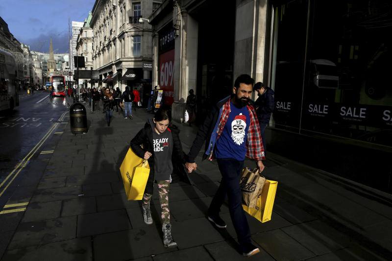 People with shopping bags walk on Oxford street in a last day before Christmas in central London, England, Tuesday, Dec. 24, 2019. (AP Photo/Petros Karadjias)