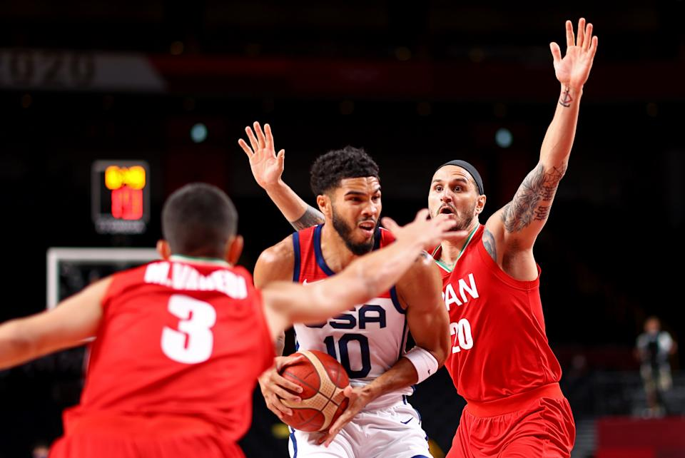Iran players Mohammadsina Vahedi (left) and Miichael Rostampour surround the United States' Jayson Tatum during the men's basketball match at the 2020 Tokyo Olympics.