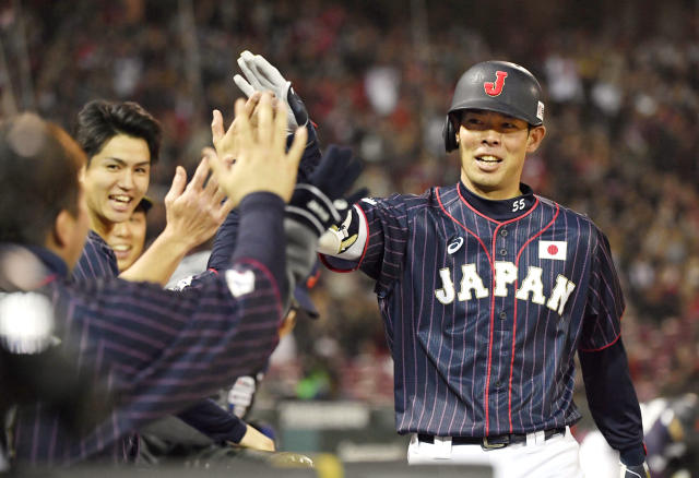 All Japan's Shogo Akiyama, right, is celebrated by teammates after hitting an inside-the-park home run off MLB All-Star pitcher Collin McHugh of the Houston Astros in the eighth inning of Game 4 at their All-Stars Series baseball at Mazda Zoom-Zoom Stadium in Hiroshima, western Japan, Tuesday, Nov. 13, 2018. (Kyodo News via AP)