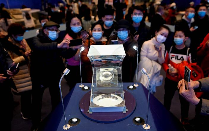 People look at lunar soil collected from China's Chang'e-5 moon mission display during an exhibition - WANG ZHAO /AFP